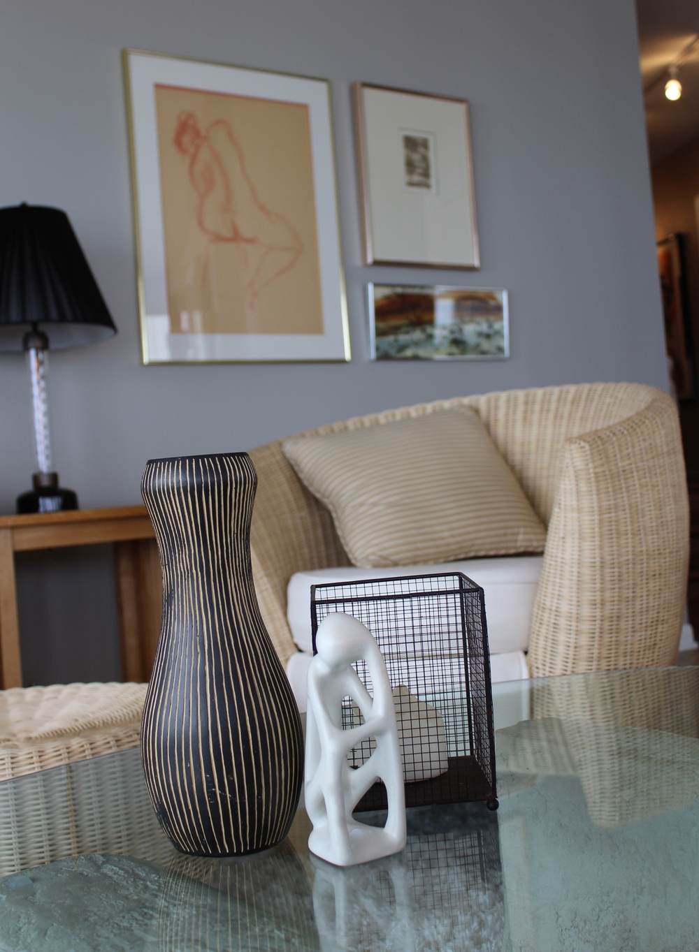 African vase, soapstone sculpture, woven chair, glass and cement coffee table, grey walls, original artwork