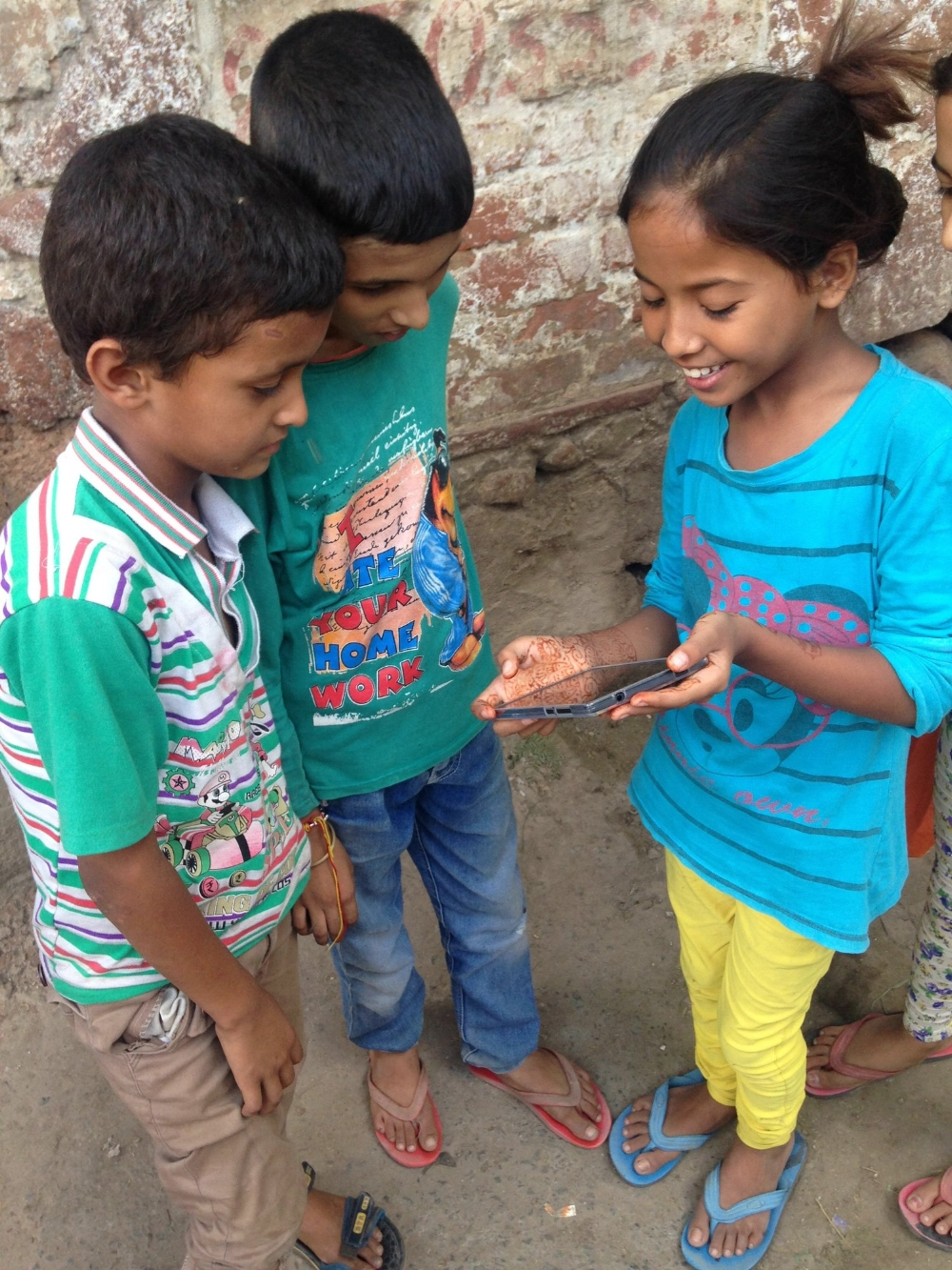 Kanchan sharing a cricket tutorial video with two boys to help them learn how to bat