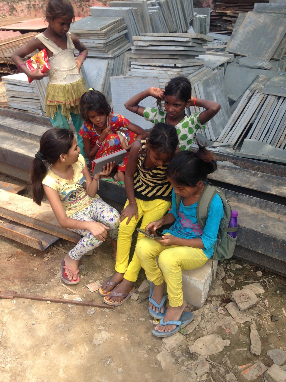 Kanchan and Geeta sharing cartoon videos with the labourers children