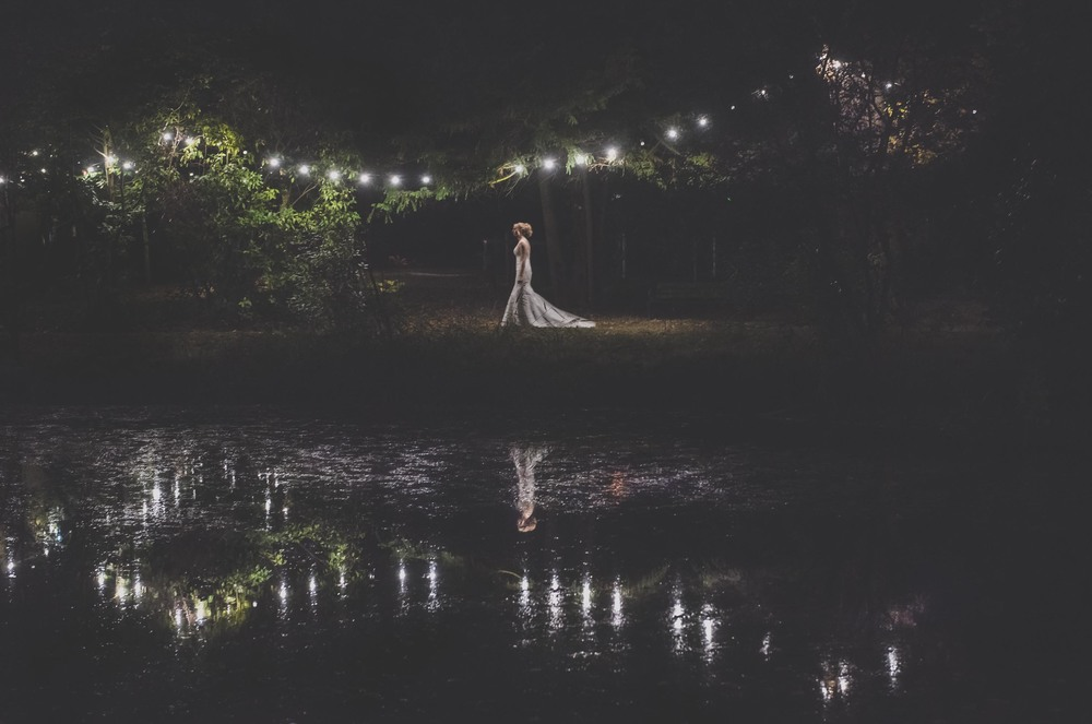 An elegant bride stood in front of a lake with fairy lights refelcting of the water Manor by the Lake, Cheltenham, Gloucestershire