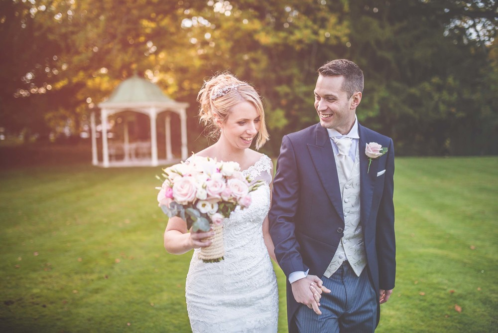 Bride and groom smile holding hands after their wedding at Manor by the Lake, Cheltenham, Gloucestershire