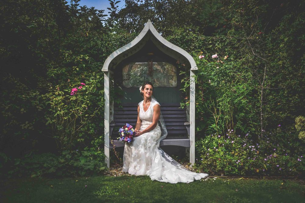 Bride sits in a pagoda surrounded by summer flowers in Bristol, UK