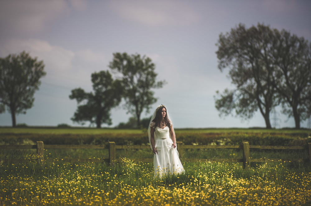 A bride stands in an English countryside field surrounded by flowers and trees on her wedding day in Warwickshire