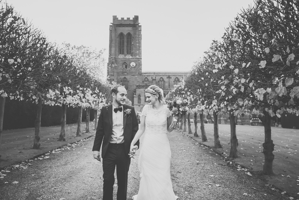 Black and white image of bride and groom leaving church hand in hand