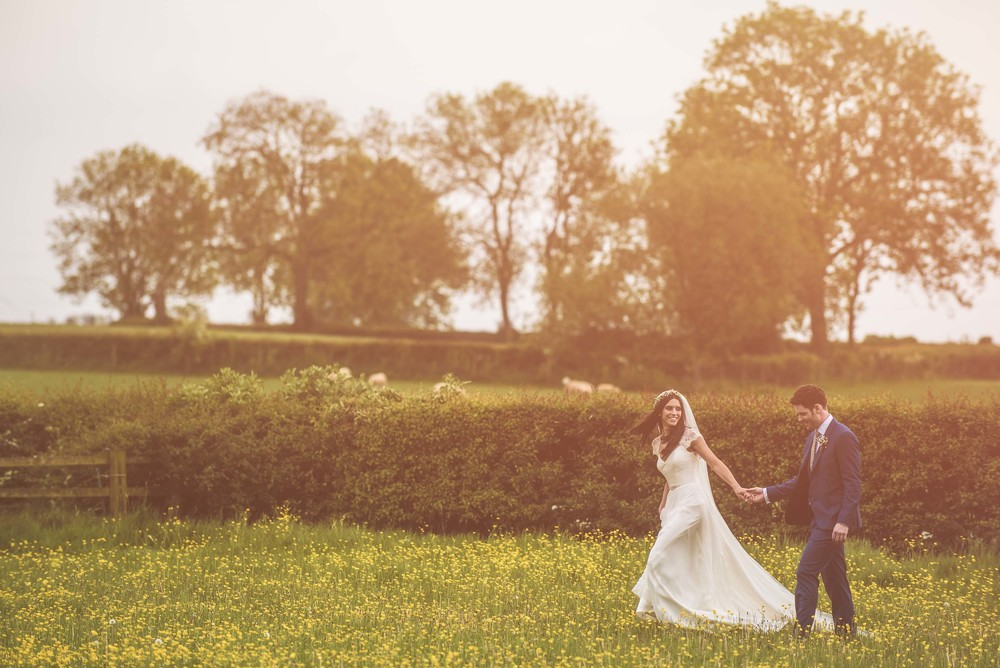 Couple take a stroll in the late summer sun after their Leicestershire wedding