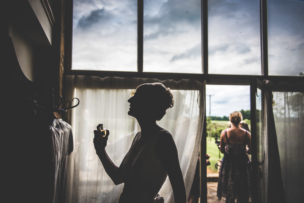 Creative image of a bride silohette putting on perfume as she gets ready for her wedding in Beachampton