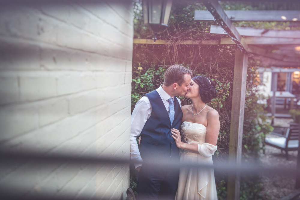 Documentary, candid photograph of a bride and groom embrasing on their wedding day in Tewkesbury, Gloucestershire