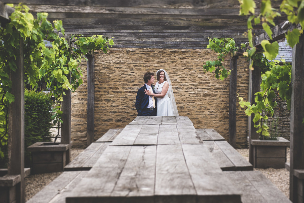 Happy newlyweds leaning against a wall in Lechlade, Gloucestershire