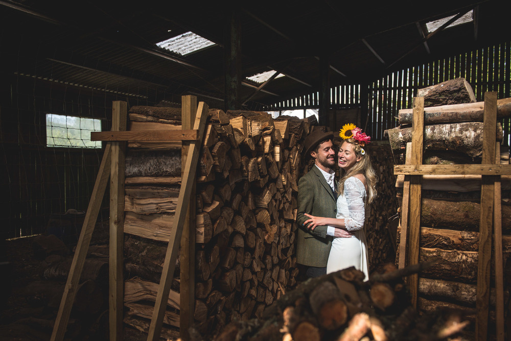 Bride and groom celebrate their humanist wedding ceremony by cuddling and laughing in a barn in Devon, UK