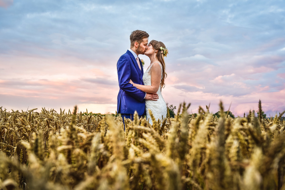 Bride and groom kiss in a corn field during sunset at Swallows Nest Barn, Sherbourne, Warwick, Warickshire, UK
