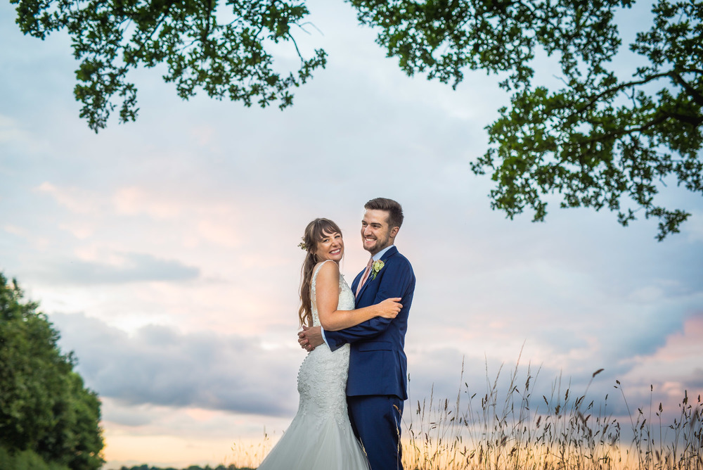 Smiling bride and groom embrace in a field at sunset during their Warwickshire wedding