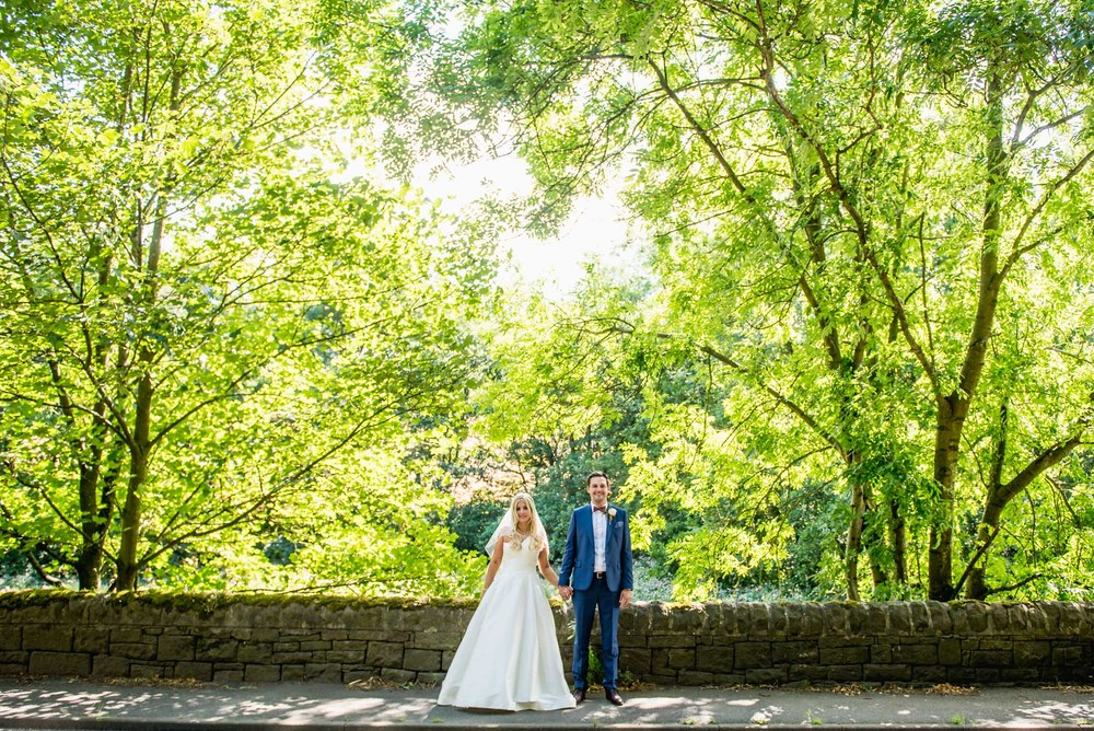 Stylish and happy bride and groom standing holding hands surrounded by trees in Derbyshire, UK