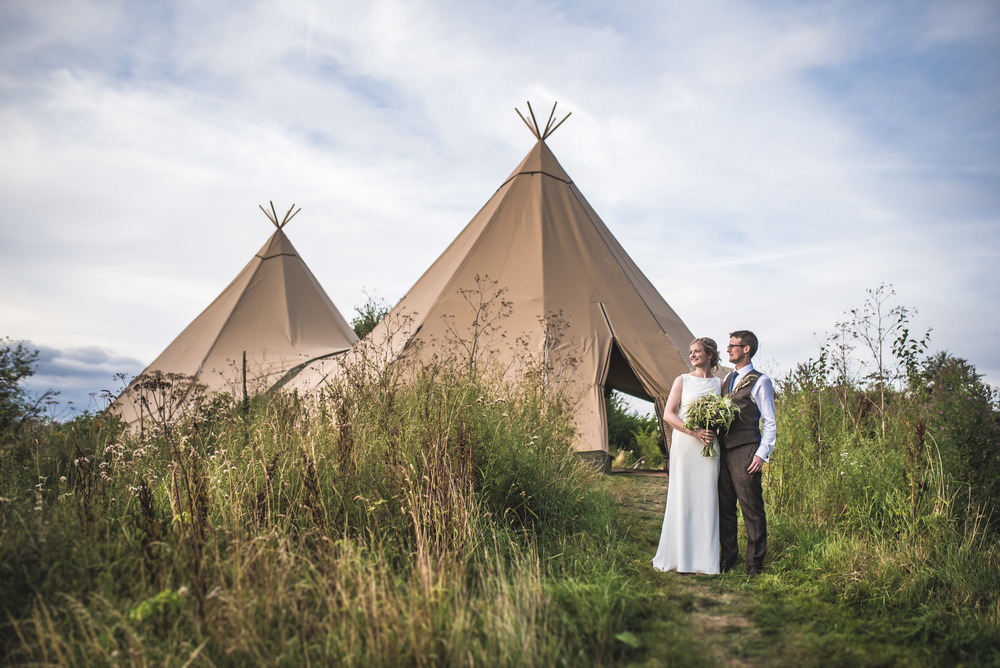 Romantic alternative wedding couple outside their tipi wedding in the Cotswolds , Gloucestershire