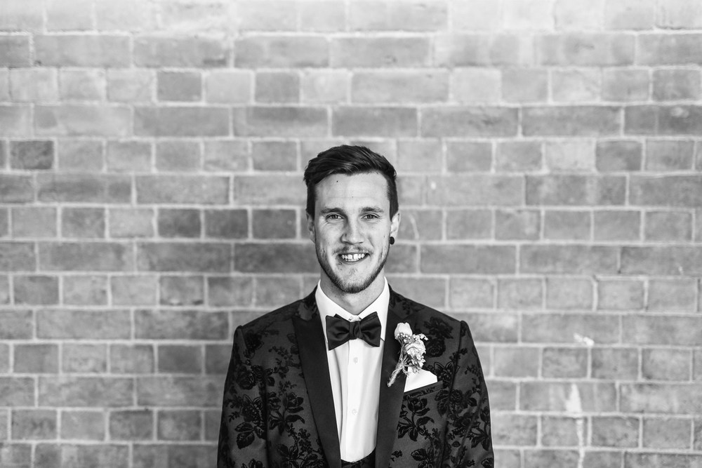 Portrait of a groom standing against a wall smiling looking at the camera