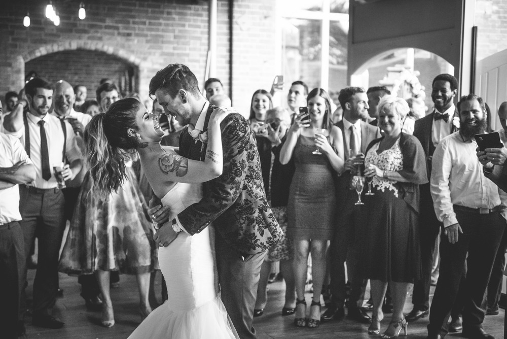 An alternative bride & groom that love tattoos laugh during their first dance watched by family and friends