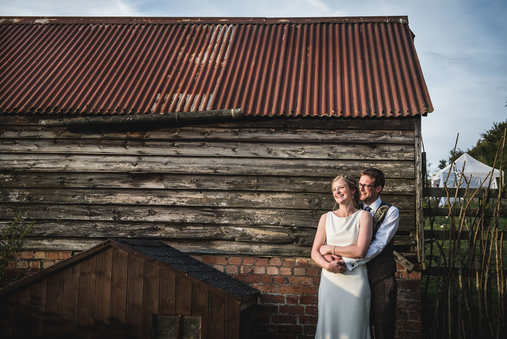 wedding couple view the sunset from a barn at Home Farm, Beechampton, Milton Keynes, Buckinghamshire