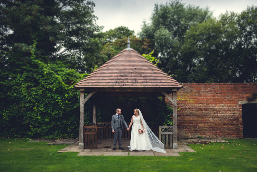 Bride and groom in a Pergola at Hatherley Manor Hotel, Cheltenham, Gloucestershire