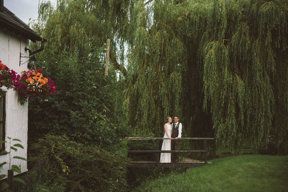 bride and groom on a bridge with willow tree, cotswold wedding