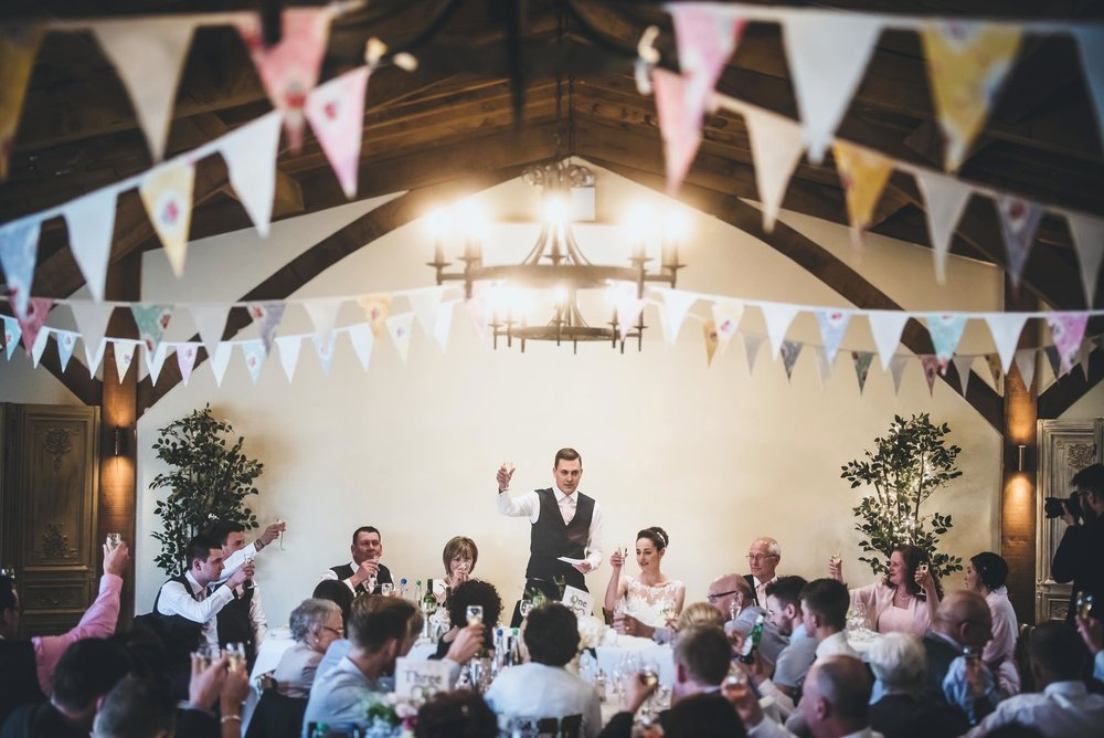 Groom makes a toast during his wedding speach surrounded by wonderful traditional bunting