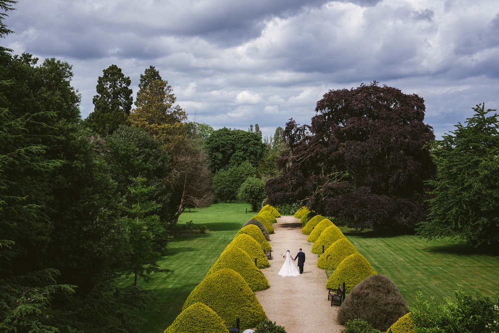 Bride and Groom enjoy the gardens at Manor by the Lake, Cheltenham