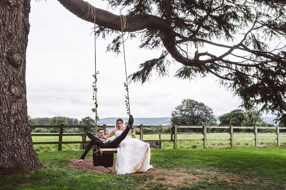 newlyweds enjoy fun on a swing at Eastington Park, Stonehouse, Gloucestershire