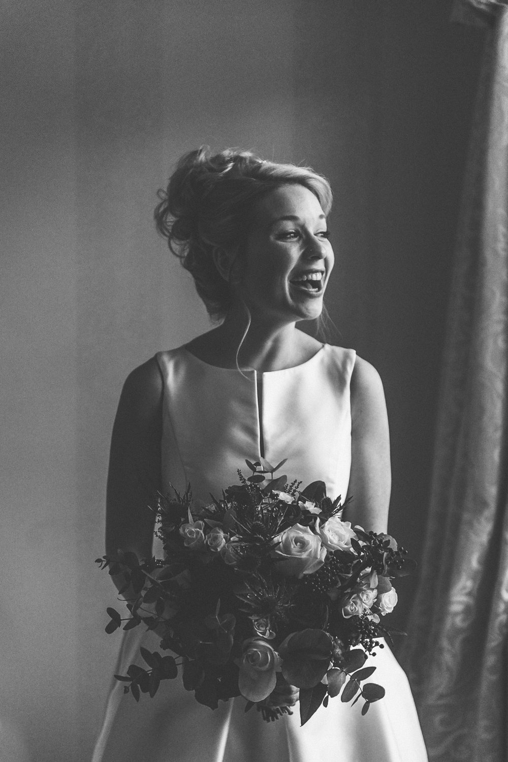 Bride laughing at her friends during bridal prep