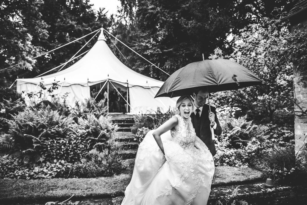 bride and groom run for cover