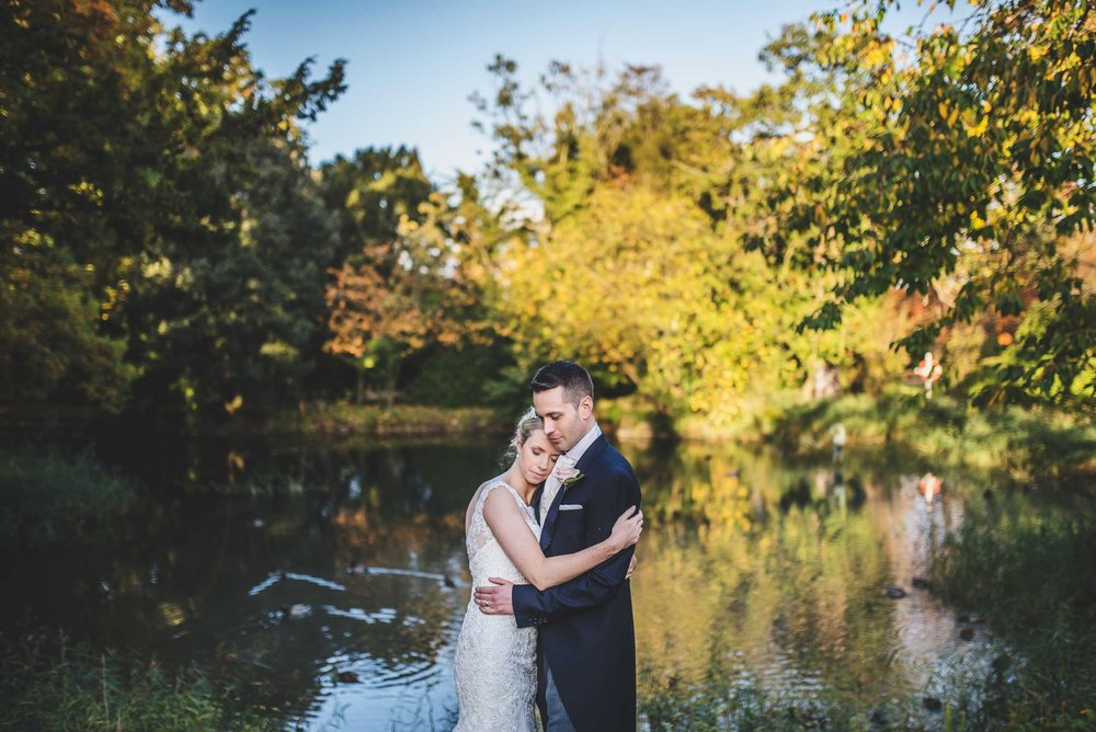 Bride and groom cuddle after their wedding at Manor by the Lake, Cheltenham, Gloucestershire