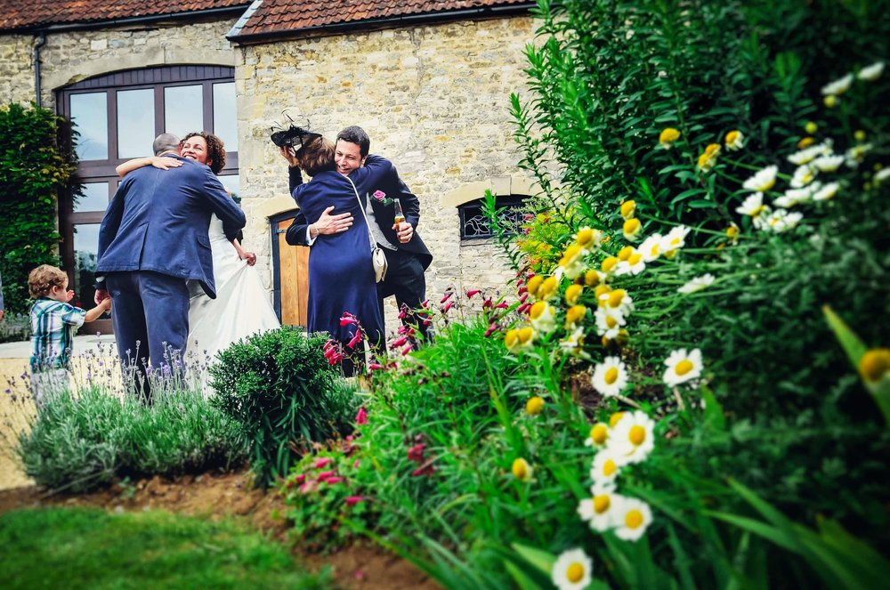 Wedding couple hug guests after their wedding in Bristol
