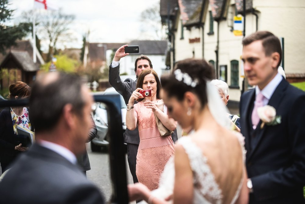 Documentary candid image of bride and groom being photographed on their wedding day