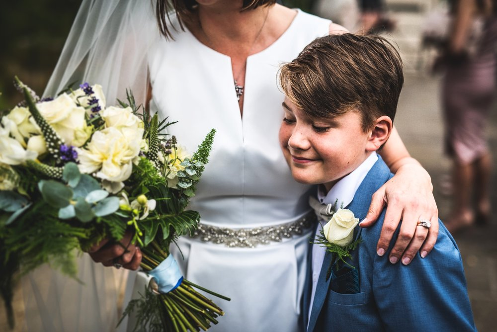 Page boy cuddling bride on her wedding day,Cotswolds, Gloucestershire