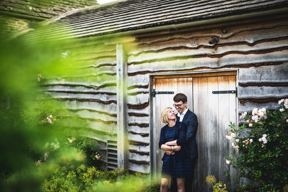 In love couple lean against a barn during a wedding in Cirencester, Gloucestershire
