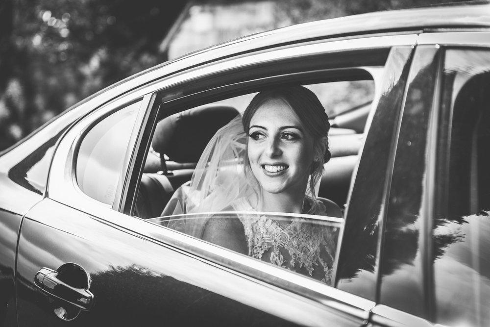 monochrome image of bride arriving to get married in the cotswolds