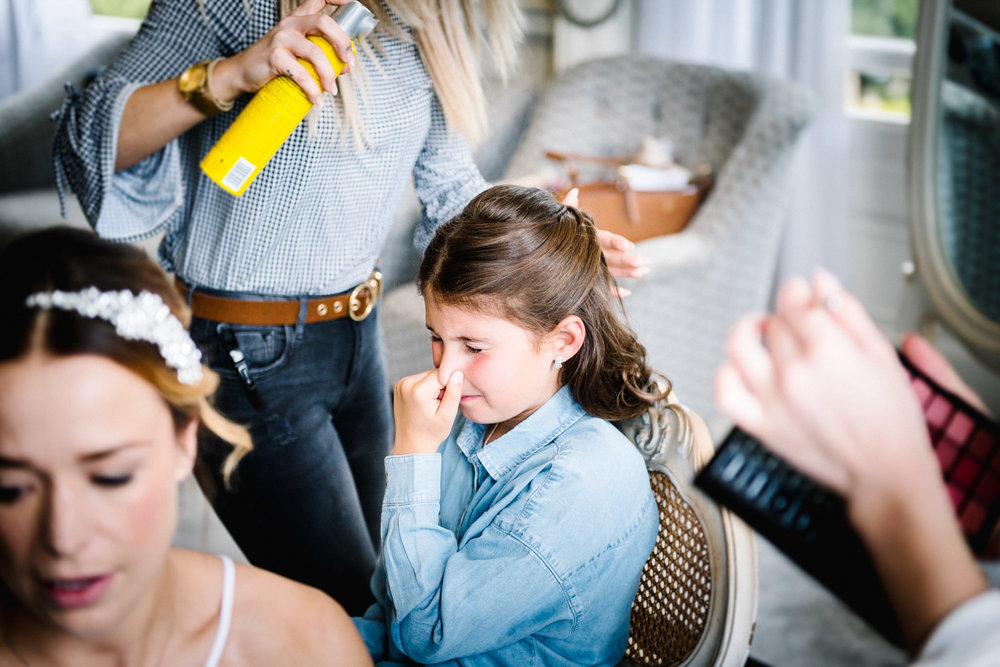 bridesmaid holds her nose from hairspray during bridal prep