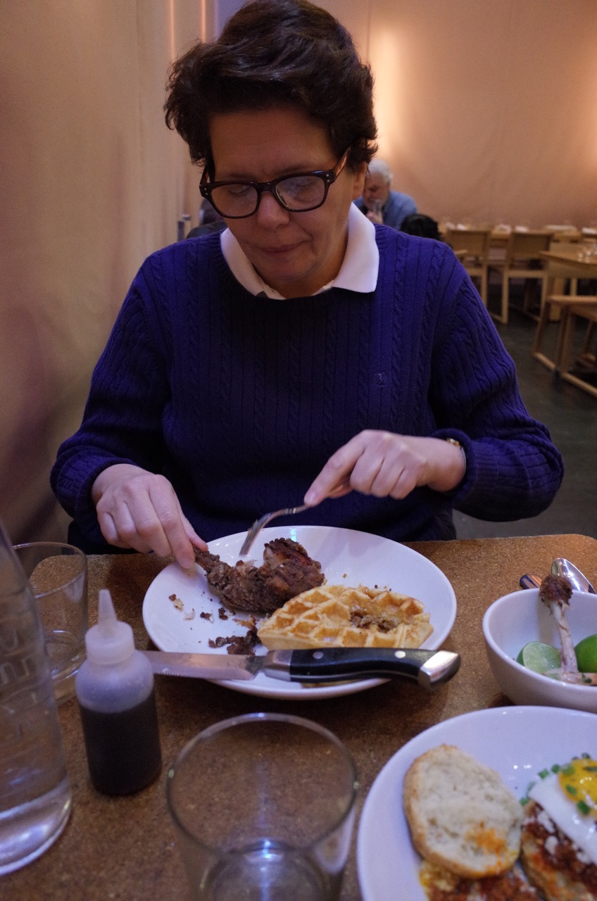 Mom cutting into her chicken and waffles at Ma Peche