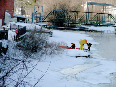 Kayakers make their way across the ice next to Trestle View Park in downtown Franklin after completing a New Year's Day run down the lower section of the Winnipesaukee River. (Roger Amsden/for The Laconia Daily Sun)