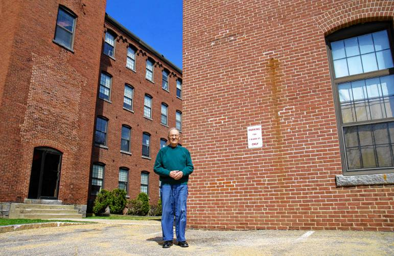 """Original river rat"" Andy Nadeau stands for a portrait outside the old Sulloway Mills buildings, where both his parents manufactured hosiery in the first half of the 20th century. Nadeau, who is 85, remembers a time when Franklin was vibrant and affluent thanks to its industry along the rivers. Elodie Reed / Monitor staff"