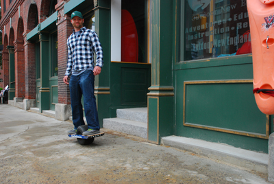 Marty Parichand, owner of Outdoor New England, rides a Onewheel electric board on the sidewalk in front of his shop in Franklin. He said the unusual devices have been a hit with the outdoor sports crowd. (Adam Drapcho/Laconia Daily Sun)