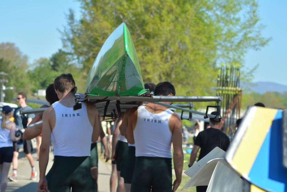 The 2V carries their boat to the dock as they launch for the grand final at the SIRA Championships.
