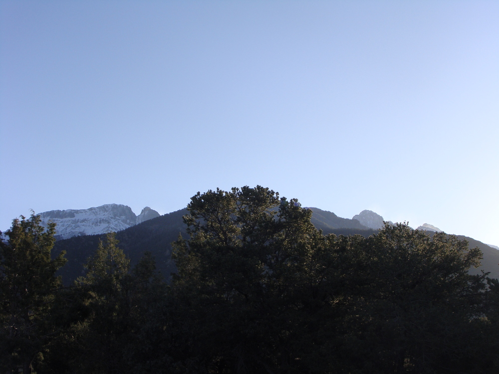 The early morning sun begins to shine on the peaks