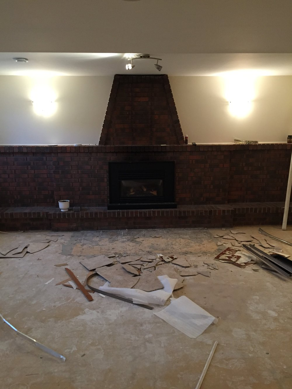 BUH BYE.. - Tiled fireplace skirt is gone. This was actually a time consuming and potentially very dangerous task. My Boyfriend Rob did this dirty work. With a hammer, chisel and a lot of patience. Most importantly, I CANNOT express the need for a pair of safety goggles MORE than with chipping out tile. You will seriously lose an eye if not. Safety first!