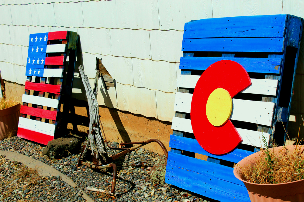 A pair of flag-decorated palettes sit at the entrance of Red Mountain Ranches.