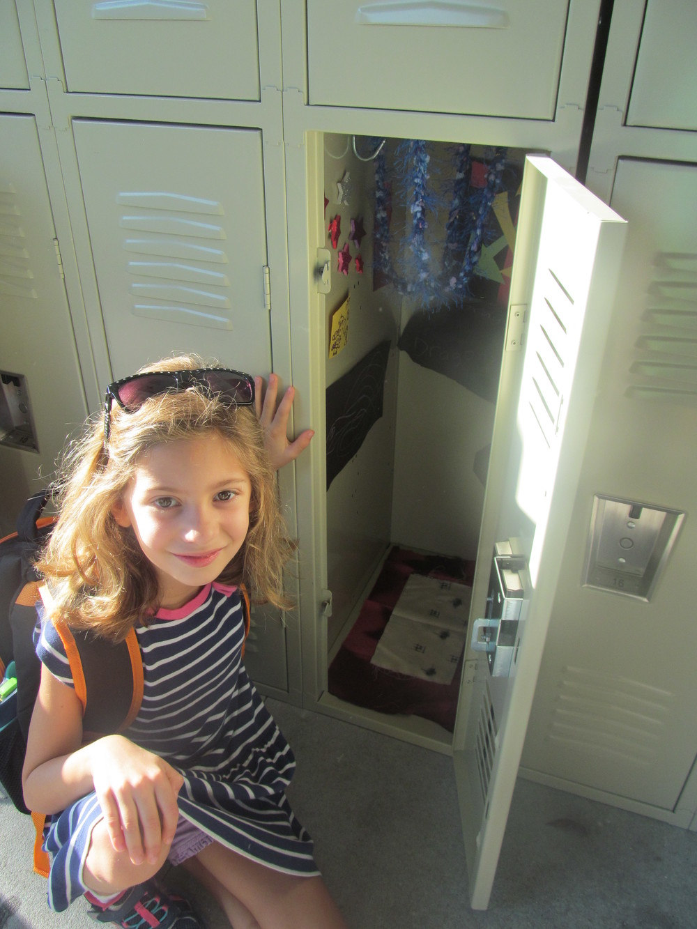 "one of the walden ""woodpeckers,"" age 7, proudly displaying her newly decorated locker."