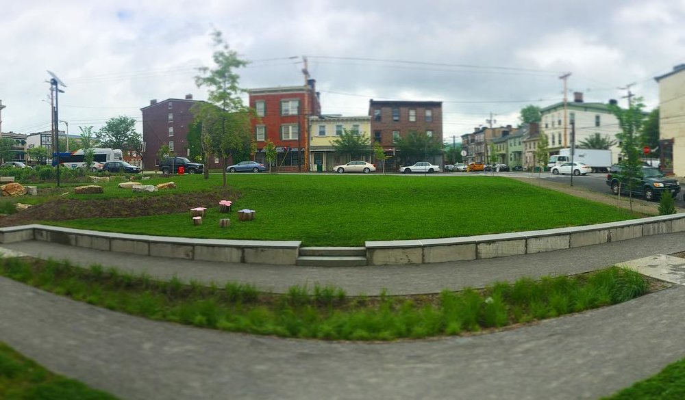 Two level clover amphitheater with seat wall and bioswale.