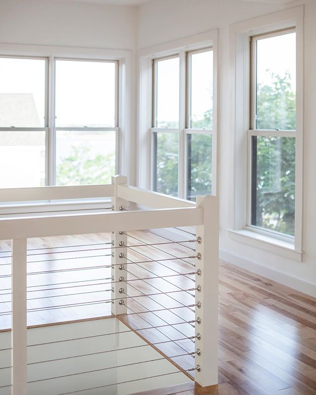 At the meeting for our #modernfarmhouse project this morning we talked a lot about cable railing as an interior detail and ultimately decided to use it as the feature in our three story staircase. While the pic you see here is all white and bright, we are going to play with contrast and throw a little black in there. Going to be 🙌❤️ Photo cred: @irvinserranophotography #designdetails #customhomes #interiorarchitecture #interiordesign #makeitnice