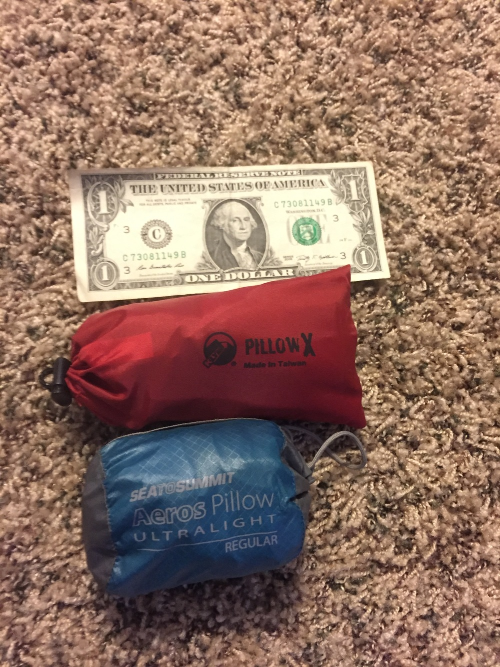 A dollar bill for scale of the size of the pillows in the stuff sacks - both pillows come with them.