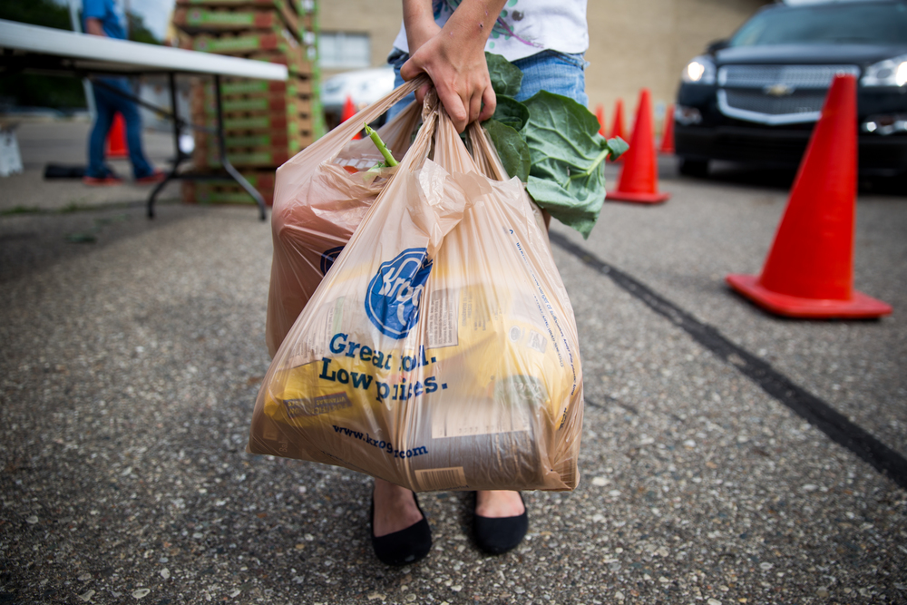 Julia Brown, 8, carries bags of groceries to be distributed while volunteering with her Girl Scout Troop 74022 during the Mobile Nutrition Pantry on Thursday, July 7, 2016 at West Court Street Church of God in West Flint. The Mobile Nutrition Pantry provides a variety of lead-mitigating foods to communities in need of good nutrition and that have limited access to grocery stores.  Check out the story: http://www.mlive.com/news/flint/index.ssf/2016/07/mobile_food_pantry_offers_lead.html