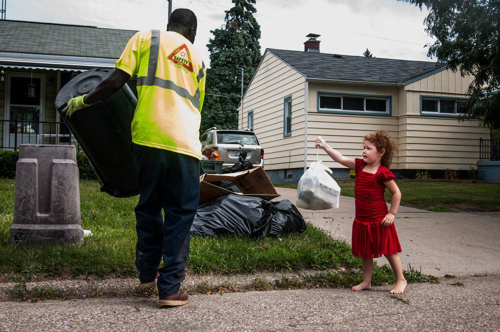 Walter Johnson, an employee of Republic Waste Services, collects garbage from Maricela Gonzalez, 4, of Flint, during his rounds on Friday, August 5, 2016 in Flint. Republic Waste Services continues to collect trash on a interim basis while the city and Flint Mayor Karen Weaver's administration worked out the details of the city's garbage contract.