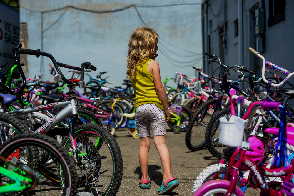 Trinity Jackson, 5, of Flint, looks down the rows of bicycles in the back parking lot of Krystal Jo's Diner for the business's Second Annual Bicycle Giveaway on Sunday, Aug. 28, 2016 in Flint. Over 150 bicycles were collected to giveaway to children in the community through a raffle.