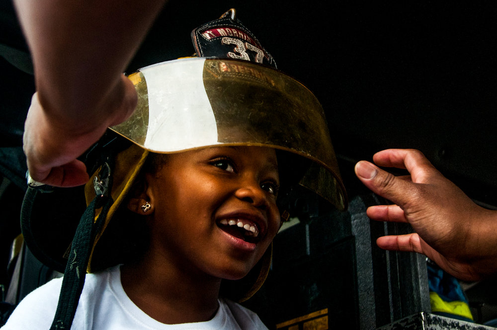 Atari Richardson, 6, of Flint, tries on a firefighter helmet during the Beecher Music Festival on Saturday, Aug. 13, 2016 in Mount Morris.
